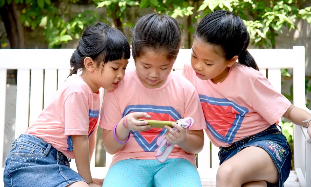 three young girls look at a smartphone